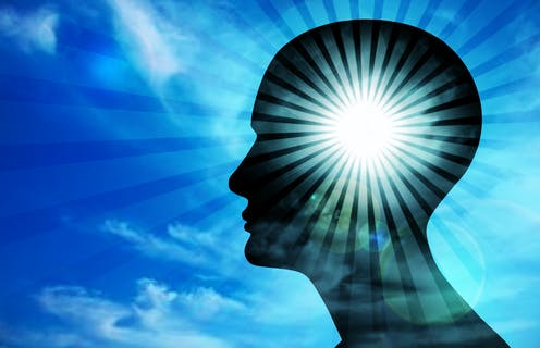 An illustration of a person's head in silhouette against a blue sky that is illuminated with a ray of light emanating outwards.