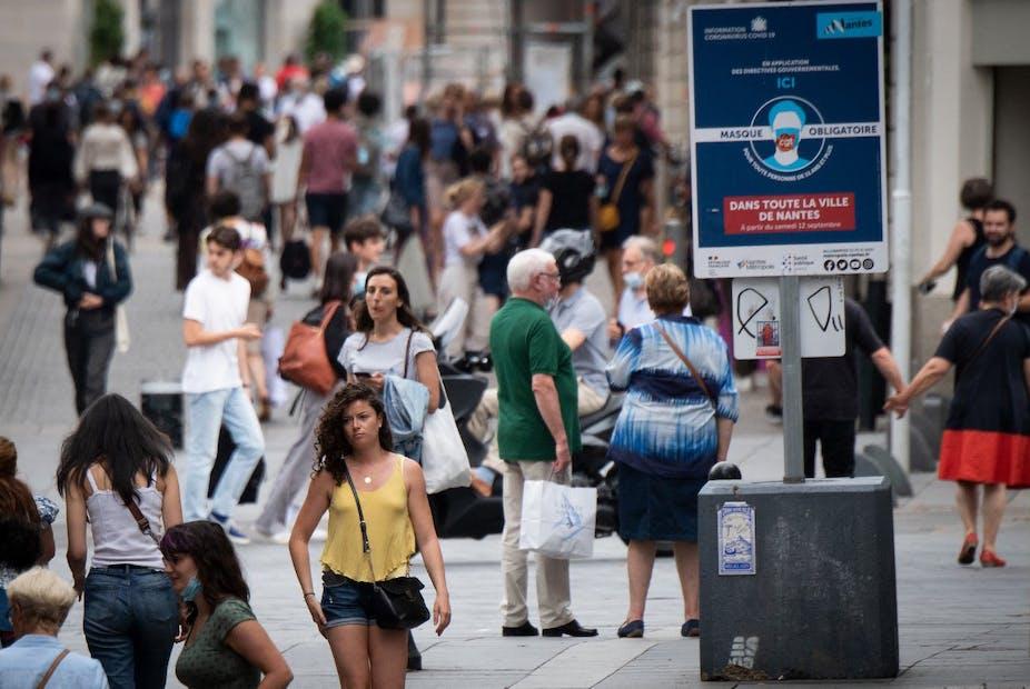 Photo d'une foule de passants sans masque, sous un panneau «masques obligatoires»