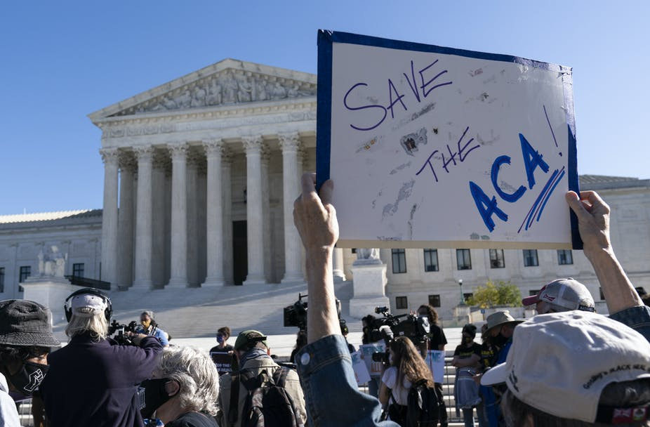 """In the foreground is a handwritten sign, reading """"Save the ACA."""" The Supreme Court building is in the background."""