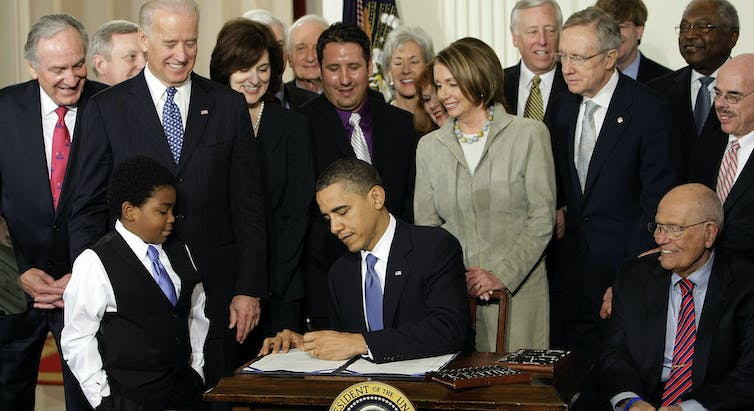 President Barack Obama is surrounded by onlookers as he signs a document. Joe Biden, Nancy Pelosi and a young Black boy in a vest and tie are part of the crowd.