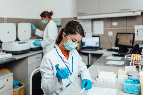 Lab technicians work while wearing masks.