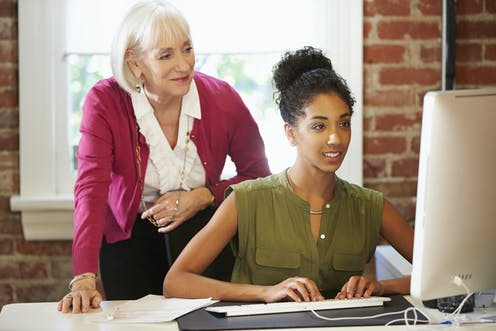 Older woman mentoring a younger women looks over her shoulder as she works at a PC