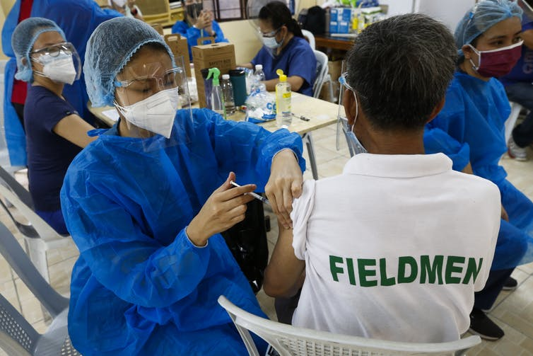 A health worker vaccinates a citizen with the Sinovac COVID-19 vaccine in the Philippines