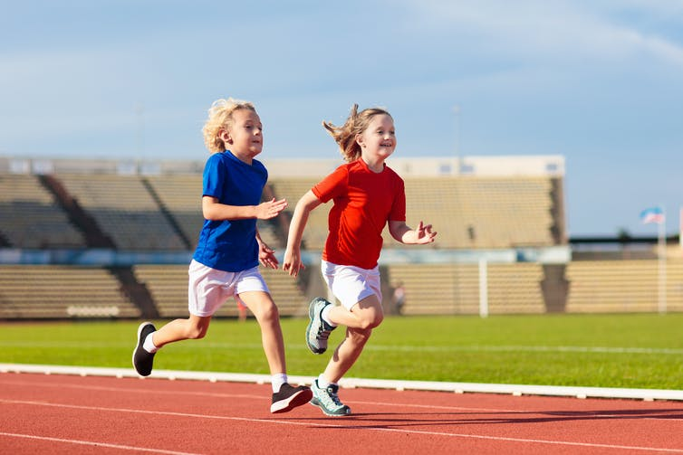 Two kids running on a track