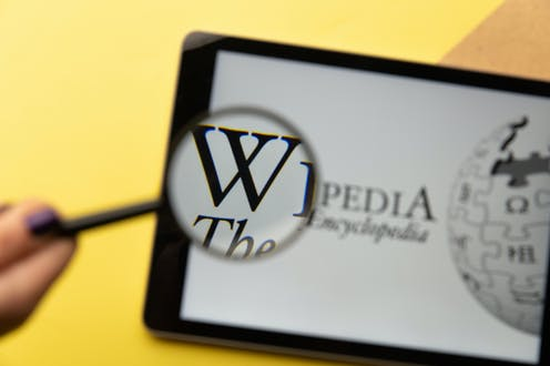 Lupa sobre página de Wikipedia en una tableta.