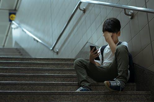 Niño con móvil en escalera con gesto apesadumbrado.