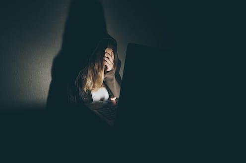 Mujer con la mano tapando el rostro ante un ordenador en penumbra.