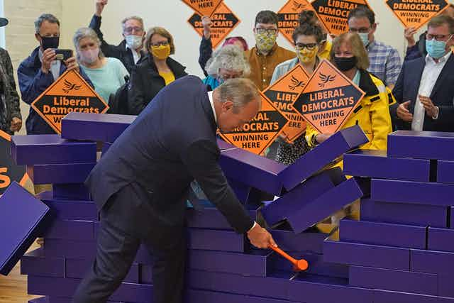 Lib Dem leader Ed Davey uses a mallet to demolish a wall of blue bricks meant to represent the Conservatives' 'blue wall' in southern England.