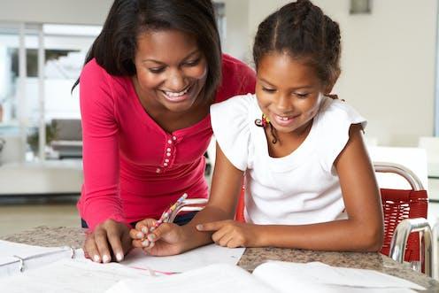 A happy mother looking over her daughter's schoolwork.
