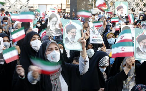 Iranian women wave flags and hold up pictures of the newly elected president Ebrahim Raisi, an arch conservative.