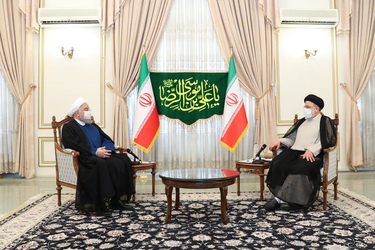 Iranian leaders sat opposite each other, wearing face masks.