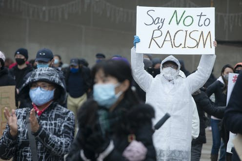 A person wearing a mask holds a sign reading Say No to Racism at a protest