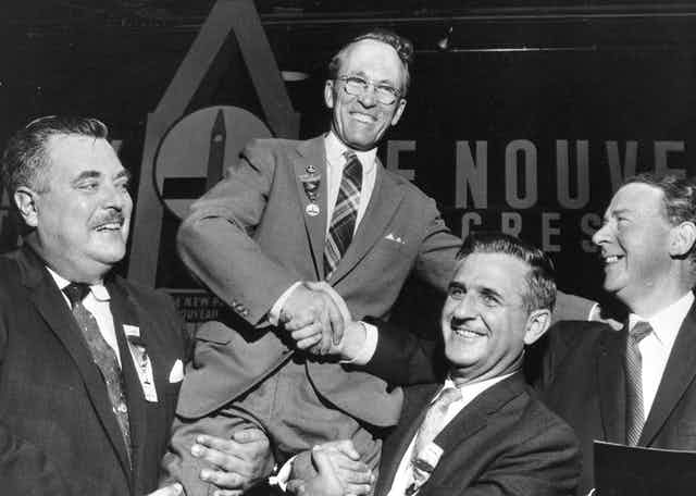 Tommy Douglas is held up by supporters in a black and white photo.