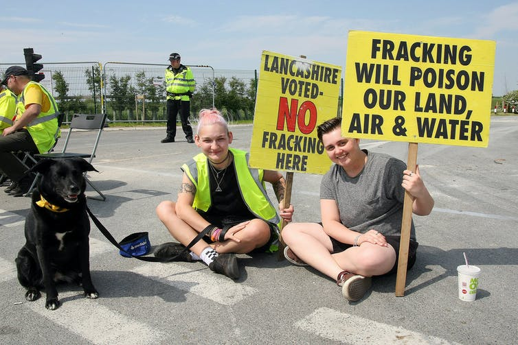 Two girls sit on the tarmac with yellow anti-fracking placards and a dog on a leash