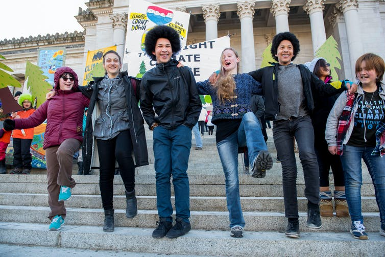 Young people stand on the steps of the Capitol building in Olympia, Washington