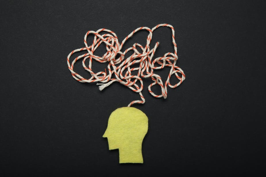 A paper cutout of the side profile of a human head, with a bundle of strings above to represent confusion.