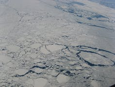 An aerial photo of pack ice with large block of ice floating on the sea and small cracks showing water between chunks of ice.