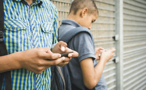 Two young people texting on their mobile phones