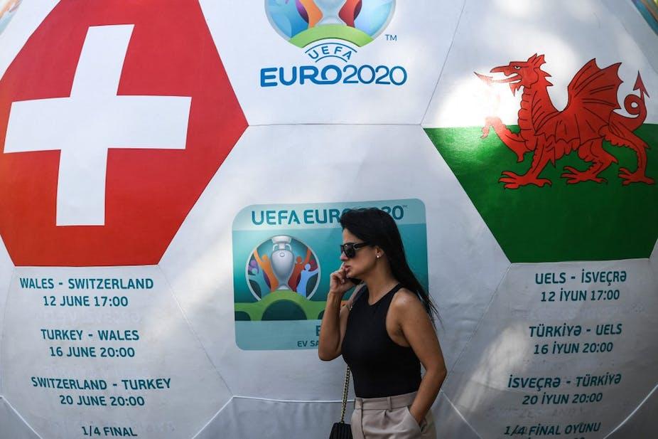 Une femme devant un ballon géant annonçant le match Pays de Galles - Suisse