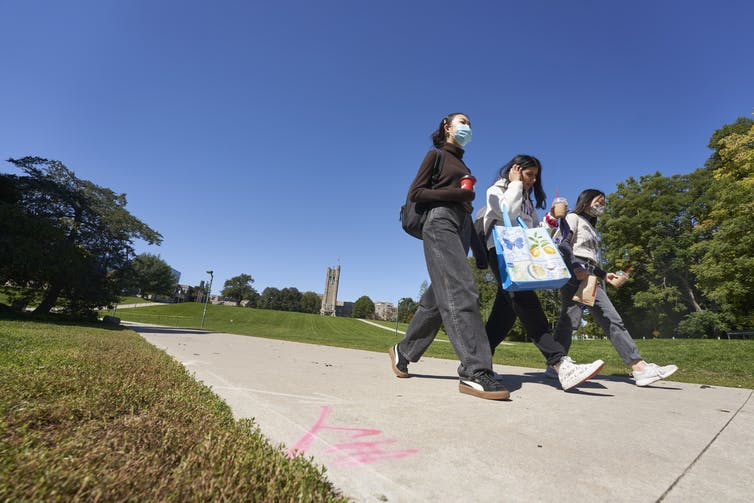 Students walking through a campus, some wearing face masks.