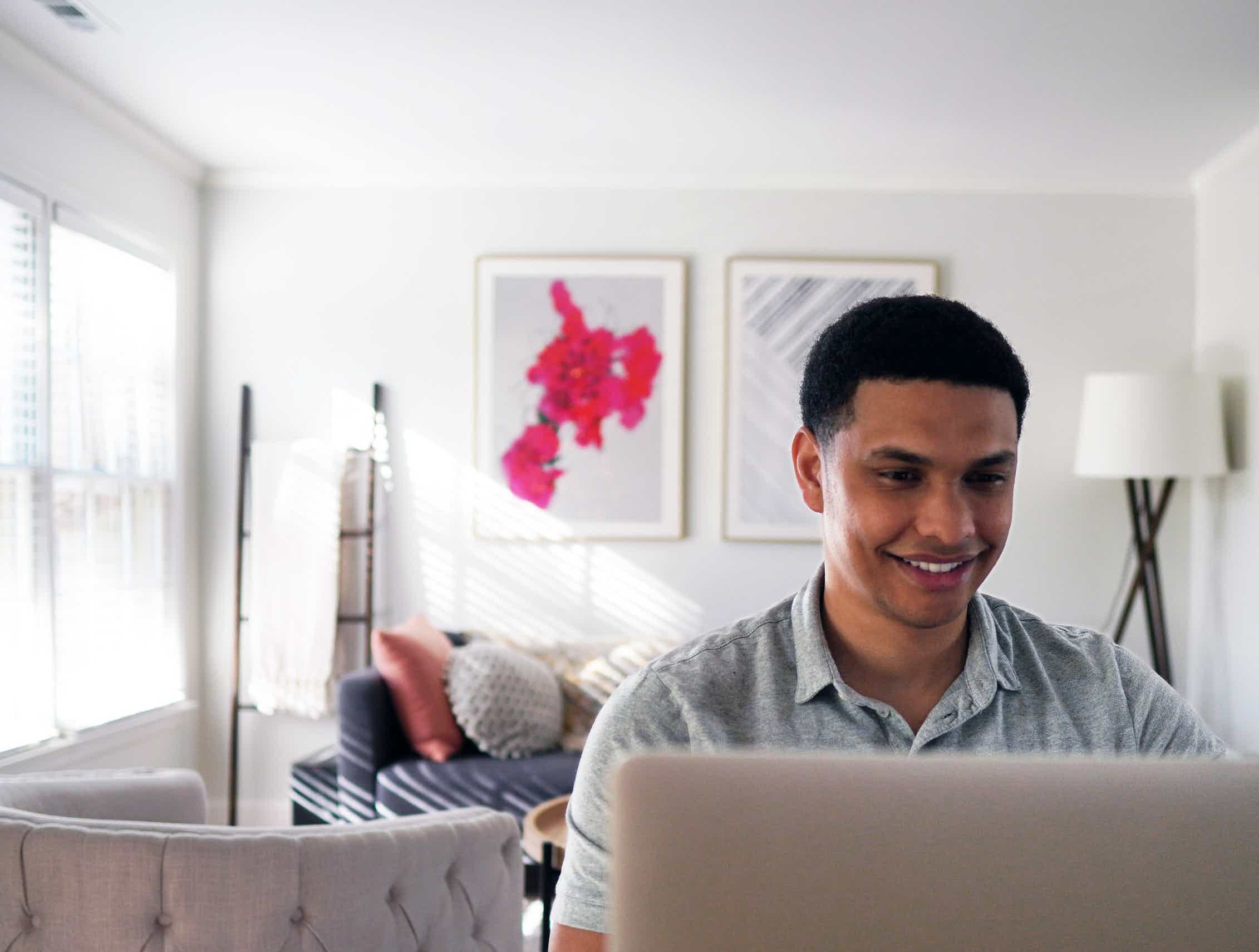 Young man sitting at a laptop.