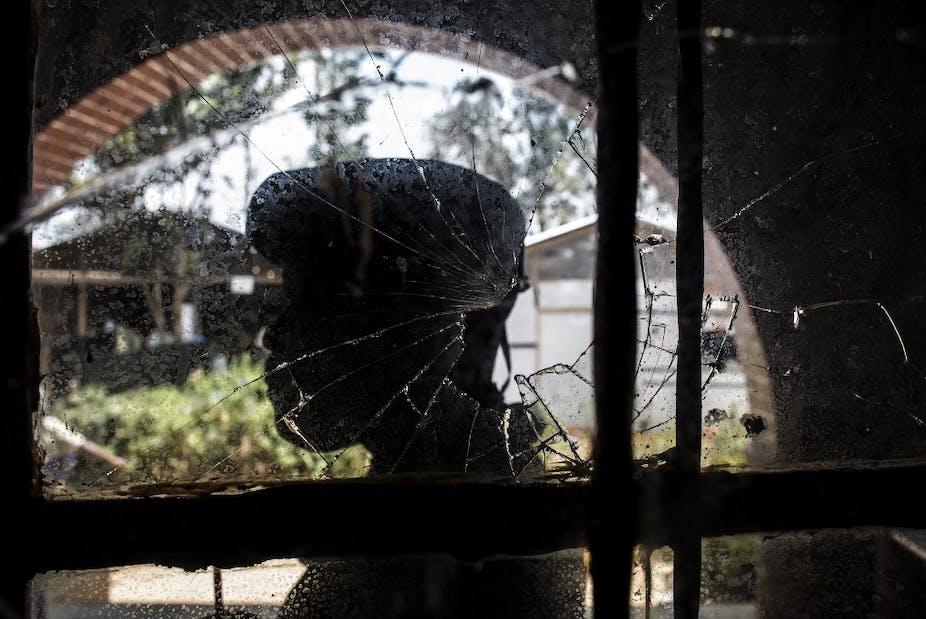 Soldat congolais derrière une vitre trouée d'une balle