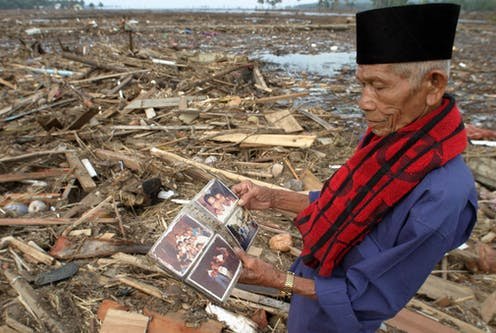 A man looks at a photo album in a destroyed village.