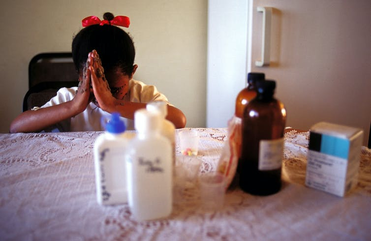 A girl with sores on her face and a red bow in her hair bows her head in prayer; pill bottles are seen in the foreground