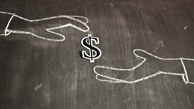 Chalk outline of two hands exchanging money