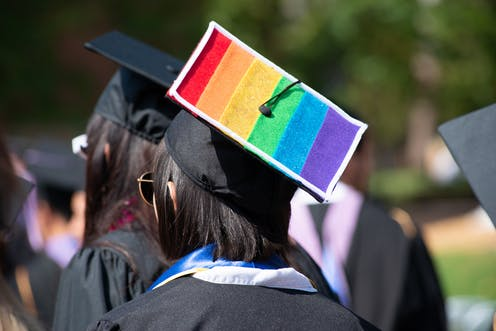 A graduating student wears a black gown and cap with the rainbow flag on it.