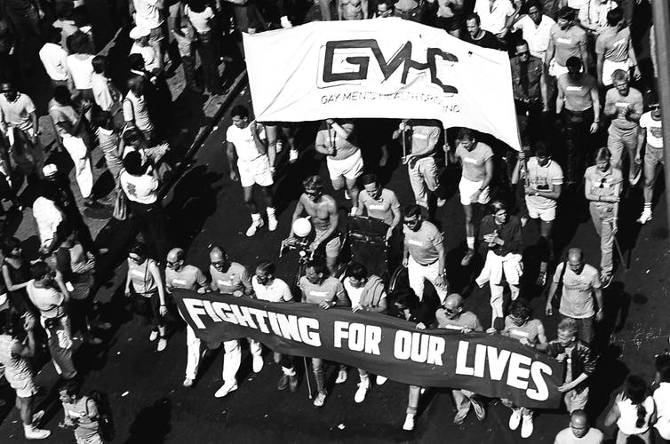 Men march shirtless holding a 'GMHC' lbanner and another that reads 'Fighting for Our Lives,'