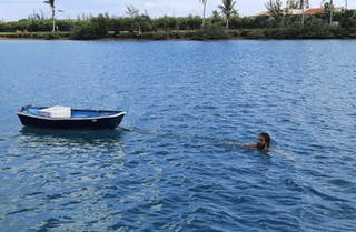 un hombre nadando cerca de la orilla remolcando un pequeño bote de remos