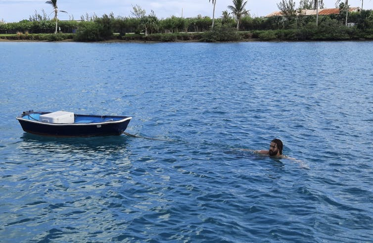 a man swimming near shore towing a small row boat