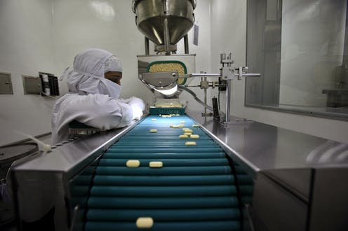 Pharmacist observing pills on a  conveyor belt in a lab.