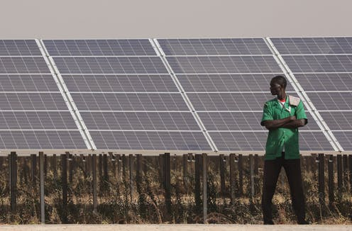 A man stands next to a solar power plant.