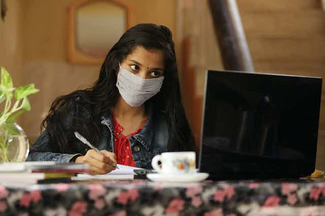 Young woman in face mask studying with computer screen and