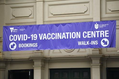A purple sign reading 'COVID-19 VACCINATION CENTRE' in Melbourne.