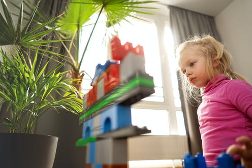 Girl concentrates on building blocks.
