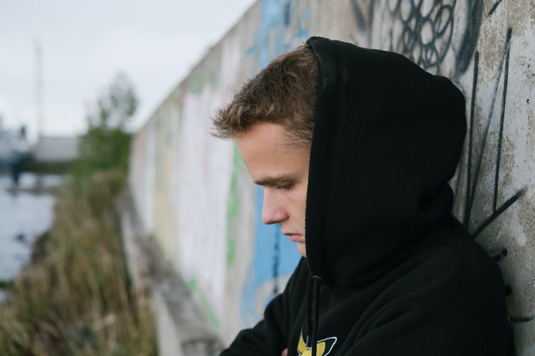 Teenage boy in a hoodie stands against a wall, looking down