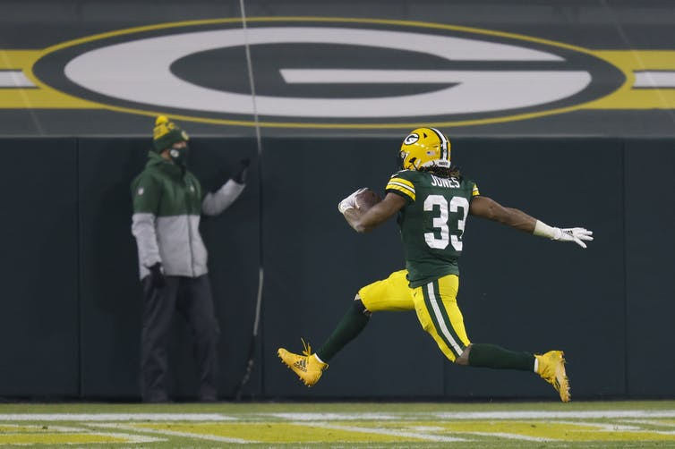 Green Bay Packer Aaron Jones running for a touchdown in a game against the Carolina Panthers on December 19 2020.