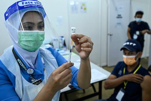 A nurse loading a syringe with COVID-19 vaccine fluid