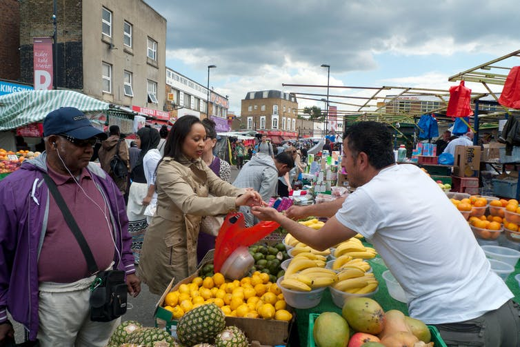 Woman pays for produce at market.