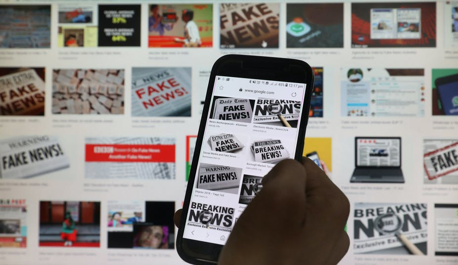 A hand scrolls the screen of a mobile phone while loading information on how to counter 'fake news'.