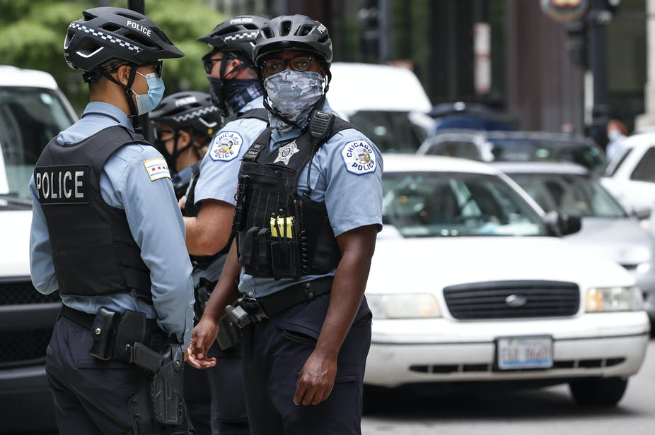 Four Chicago police officers in hard bike helmets and tactical vests standing outside during a protest.