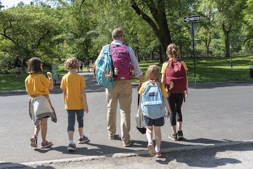 A man walks through a park with four children.