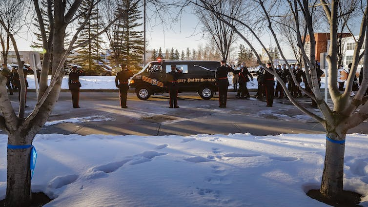 Snow covers the ground as a hearse drives past cops saluting