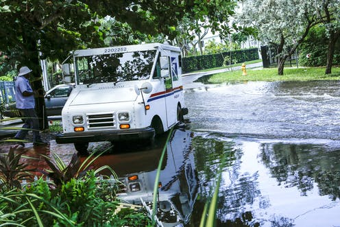 A postal truck parked at the edge of a flooded street.