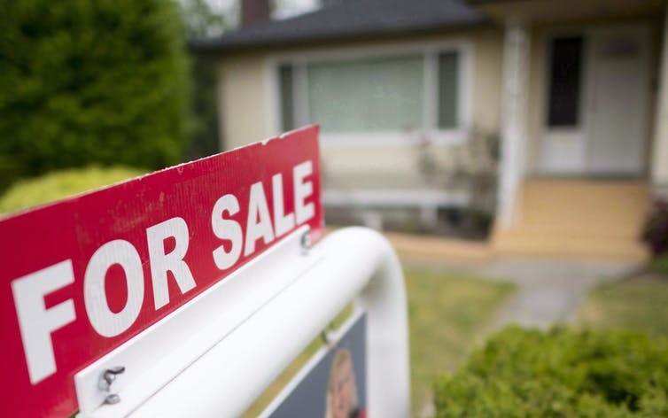 A 'For Sale' sign is pictured in front of a house