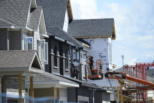 Houses are being built in the suburbs, men are on a cherry picker adding shingles
