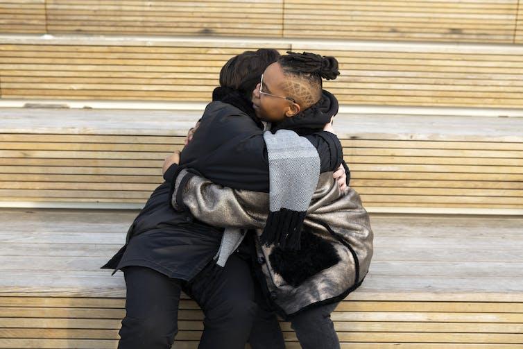 Two people sit hugging on steps